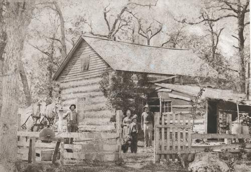 The Wright family stands in front of their log house in Denmark Township.