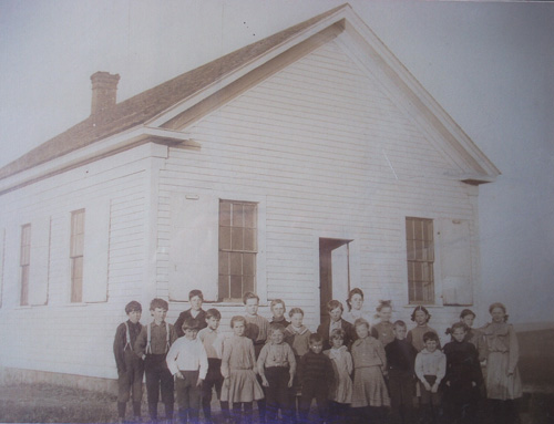 Front Row [left to right]: Percy Beecroft, Charles Beecroft, Grace Carmichael, Rollie Powell, Clint Rutherford, Clara Carmichael, Gail Powell, Lance Rutherford, Dean Ramsden, Myrtle Rutherford. Back Row [left to right]: Albert Ernest Beecroft, Ed Beecroft, Clarence Peterson, Lydia Powell, Earl armichael, Eva Masterman, Lyle Powell, Teacher Pearl Goff, Mabel Peterson, Olive Rutherford, Elsie Rutherford, Hazel Ramsden.