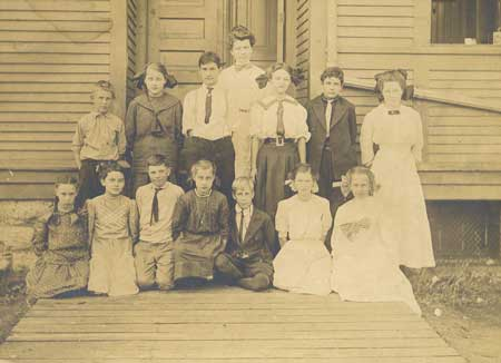 Photo of old Newport School house ca. 1908-09. Teacher was Miss Emma Glaser. Back Row, left to right: Dana McDonald, Alice Berfeldt, Leon Woods, Grace Chapelle, Clayton Smith, Marjarie Rode. Front Row, left to right: Hester Pinter, Florence Schabaker, Lyle Roberts, Margaret Berfeldt, Cecil Wygant, Helen Rode, Carinne Simmons