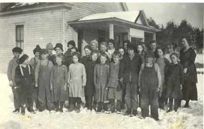 Oneka School, District #75, ca. 1910. Students are: Front row, left to right: Charles Tingley, Soe Schotl, Mary Schotl, Dorothy Tingley, Frances HOpkins, Grace Schotl, Allen Lundgren, Raymond Kuno, and Tony Schotl. Second row: George Gessner, Alfred Anderson, Agnes Tingley, Catherine Lundgren, Kathleen Rutherford, Lutella Tingley, Kate Schotl, Inez Taylor, and Myrtle Kuno. Third row: Lionel Hopkins, Maurice Gessner, Max Davis, Theodore Gessner, Gladys Shfer. The teacher is Ethel Erickson.